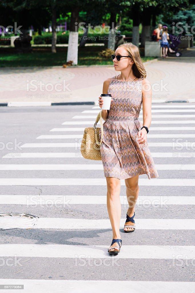 Young brunette woman in dress crossing the street with coffee Lizenzfreies stock-foto