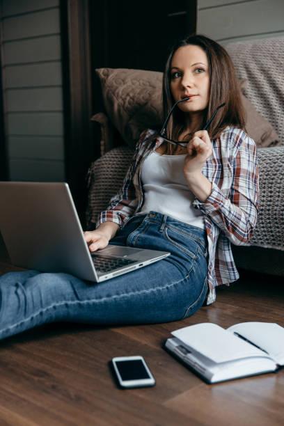 joven morena mujer en gafas sentada en el suelo y trabajando con portátil en casa. mujer independiente de la tarea. - zoom meeting fotografías e imágenes de stock