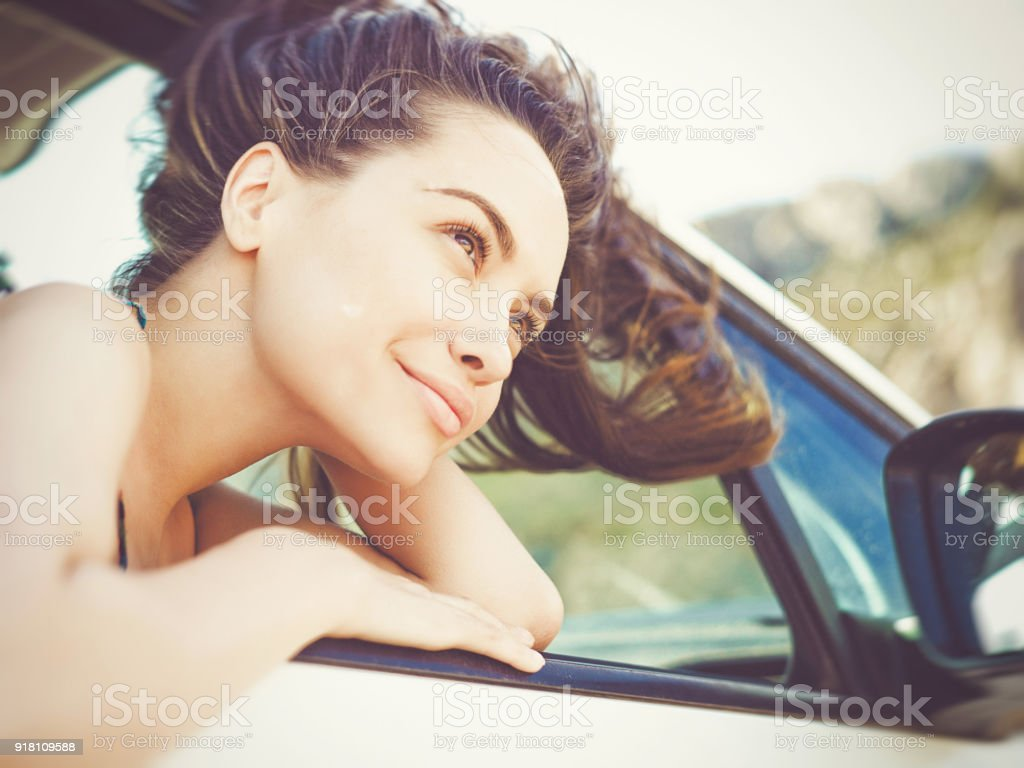 Young brunette woman in the car on the beach stock photo