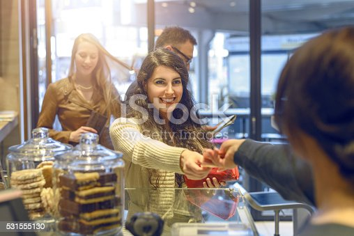istock Young brunette woman making payment at a till 531555130
