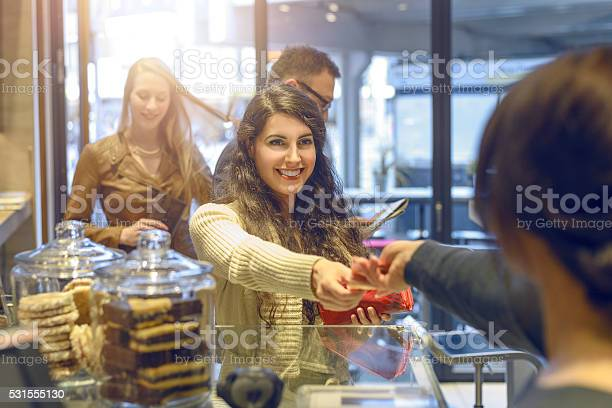 Young brunette woman making payment at a till picture id531555130?b=1&k=6&m=531555130&s=612x612&h=zck g8t1yuhv wrcnizbfpwo5k7xnpwwm4qmgs0itru=