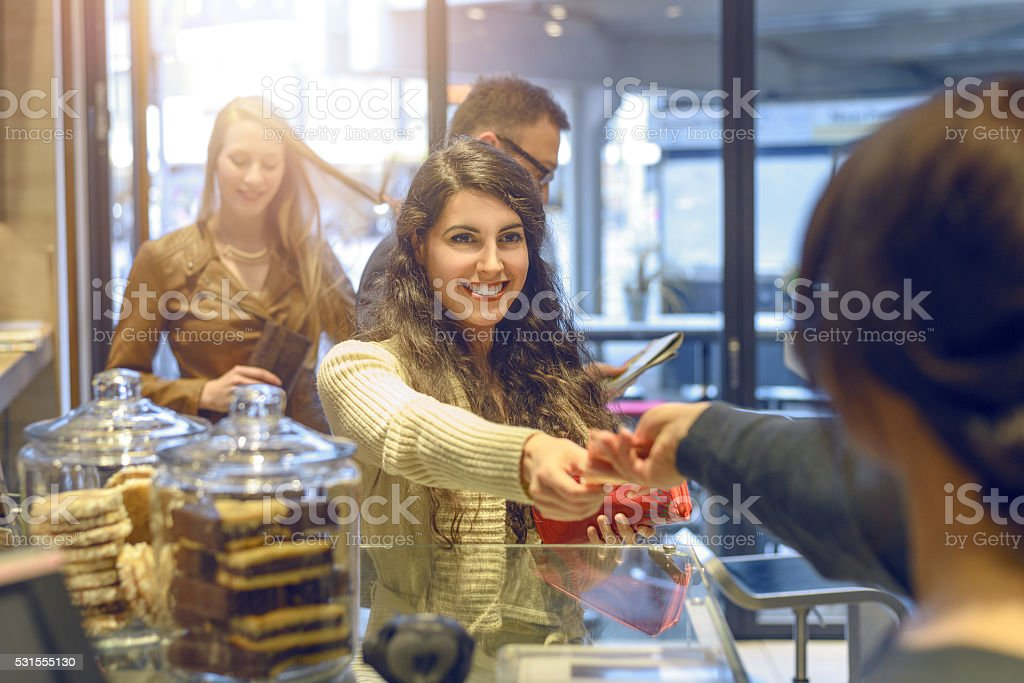 Young brunette woman making payment at a till stock photo