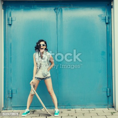 Funky girl posing with skateboard. Lifestyle outdoor portrait