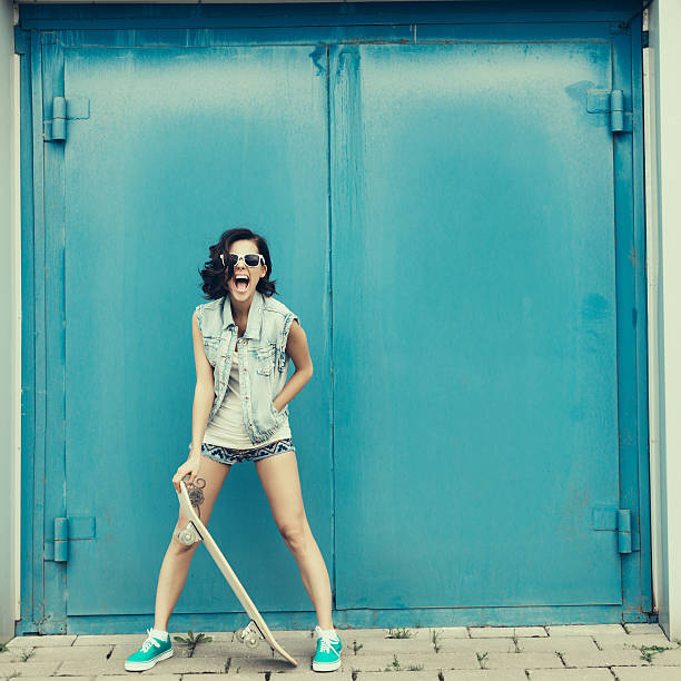 Young brunette woman posing with skateboard stock photo