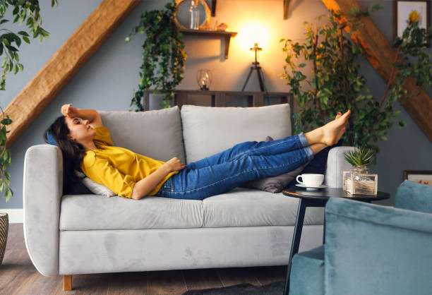 Young brunette woman relaxing on the couch after a long day stock photo