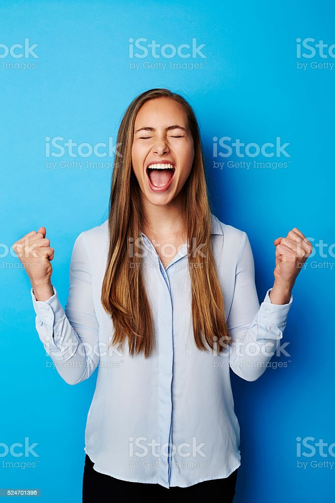Young brunette woman screaming in blue studio stock photo