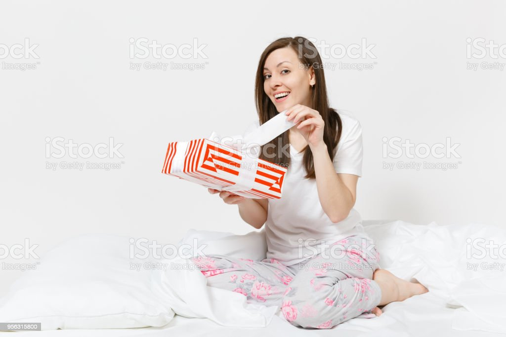 Young brunette woman sitting in bed with red striped gift box, white...