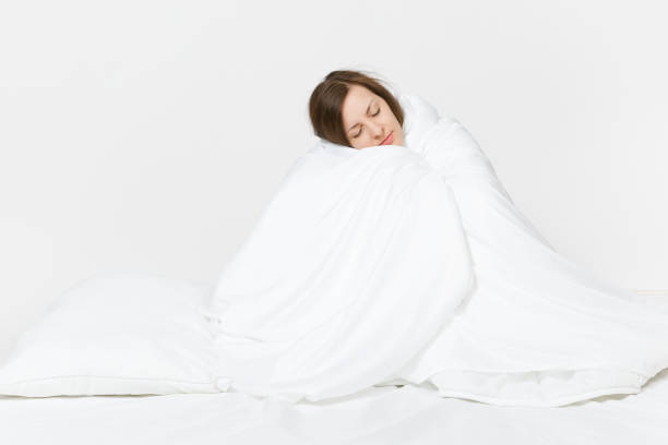 Young brunette woman sitting in bed with white sheet, pillow, wrapping in blanket on white background. Beauty female spending time in room. Rest, relax, good mood concept. Copy space for advertisement Young brunette woman sitting in bed with white sheet, pillow, wrapping in blanket on white background. Beauty female spending time in room. Rest, relax, good mood concept. Copy space to advertisement wrapped in a blanket stock pictures, royalty-free photos & images