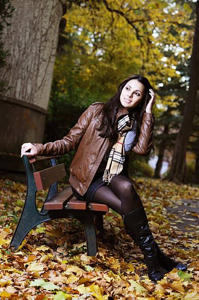 young brunette frau sitzt auf der bank und genießen sie den herbst - damen rock braun stock-fotos und bilder