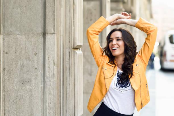 young brunette woman smiling in urban background. - lange jacken stock-fotos und bilder