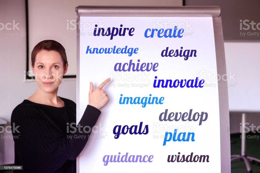 young brunette woman standing at flipchart with buisiness oriented words on it stock photo