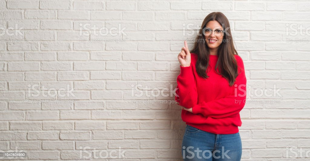 Young brunette woman standing over white brick wall showing and pointing up with finger number one while smiling confident and happy. stock photo
