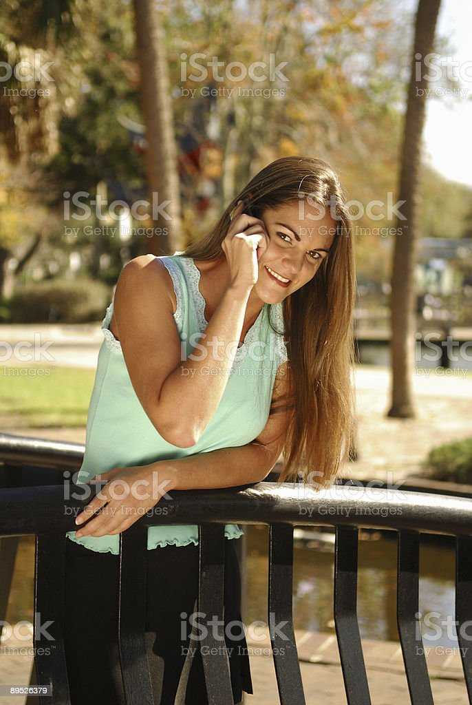 Young Brunette Woman Talking on Cell Phone in a Park royalty-free stock photo