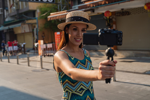 Young brunette woman using a video camera to record journey with attractive smile. Happy and excited 20s Hispanic girl traveler wear summer dress with hat waving to internet audience. Influencer and vlogging concept