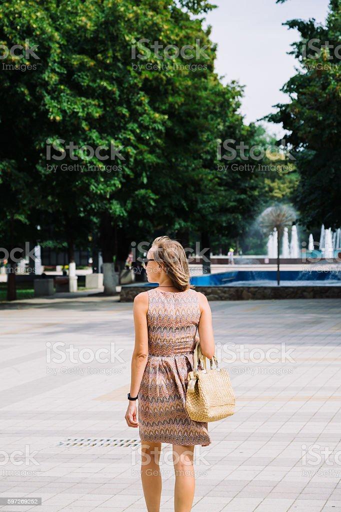 Young brunette woman walking in park against of fountain Lizenzfreies stock-foto