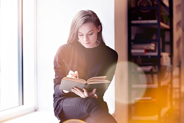 Young brunette woman with a book in a public library. stock photo