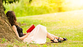 Picture of woman with a book sitting under a tree