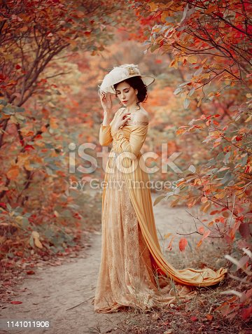 A young brunette woman with an elegant, hairstyle in a hat with a strass feathers. Lady in a yellow vintage dress walks through the autumn landscape. Artistic portrait.