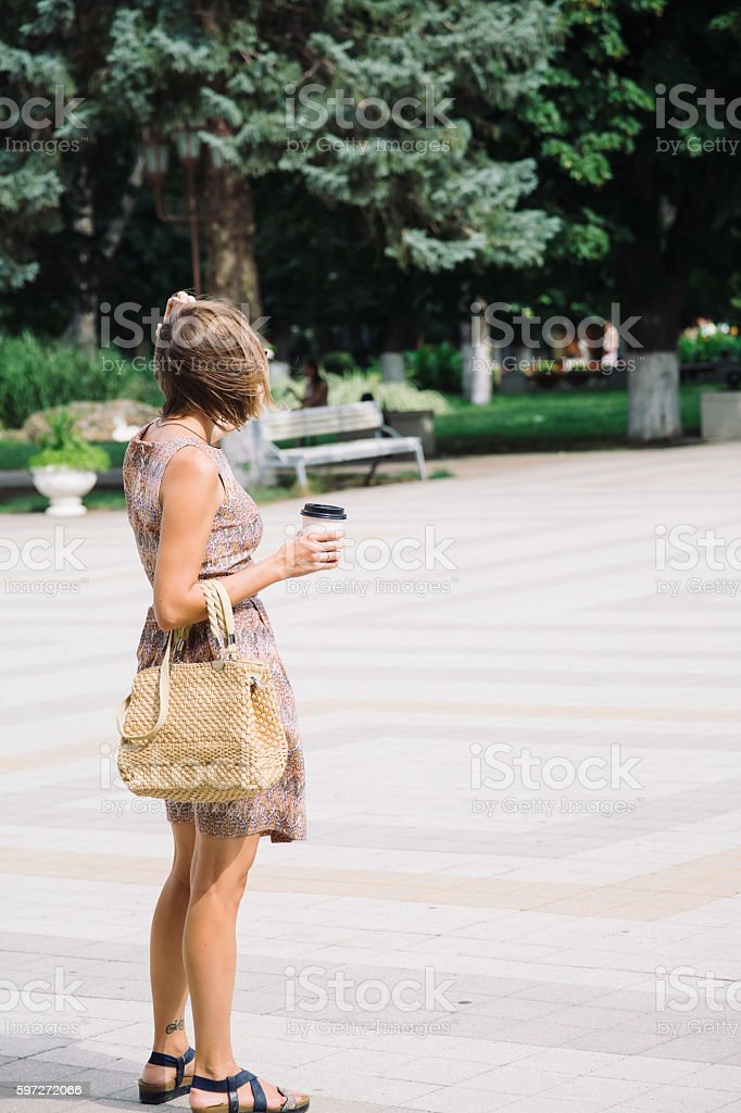 Young brunette woman with coffee cup walking in city Lizenzfreies stock-foto