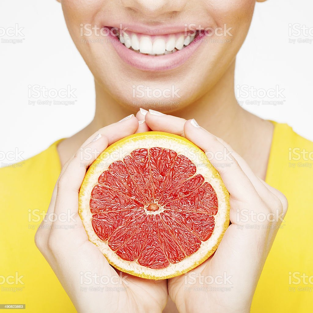Young brunette woman with grapefruit stock photo