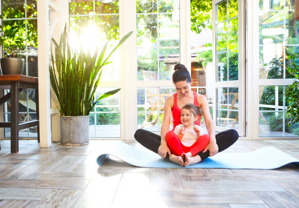 Young brunette woman with little daughter in a sporty uniform doing yoga stock photo
