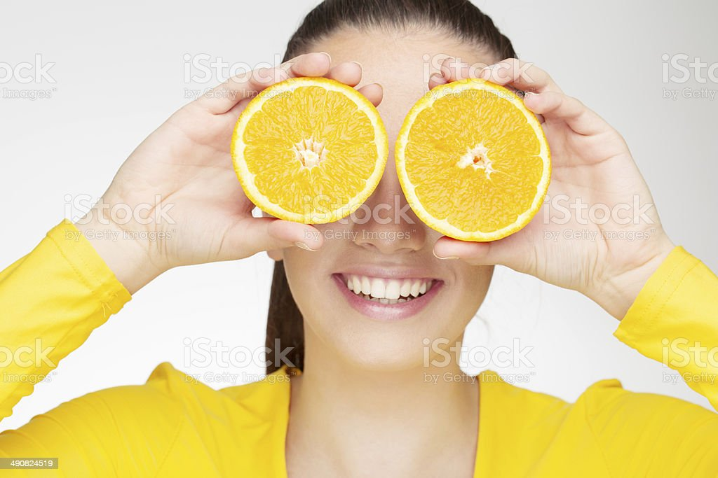 Young brunette woman with orange fruit stock photo