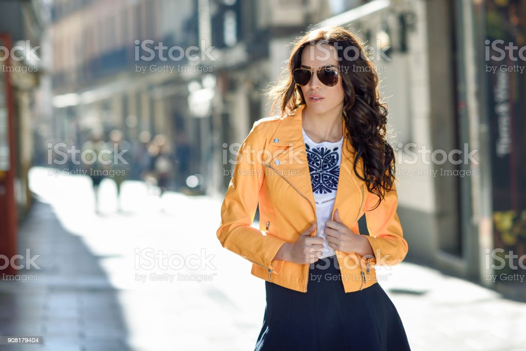 Young brunette woman with sunglasses in urban background stock photo