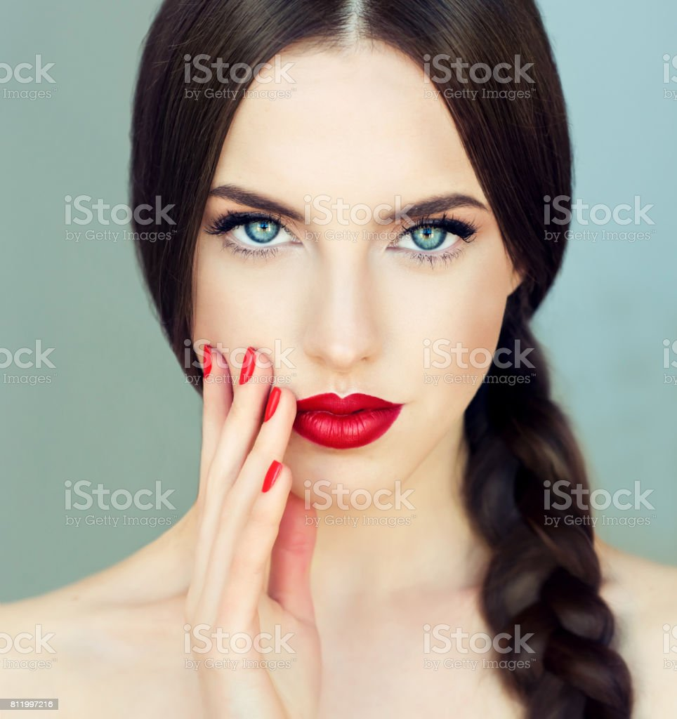 Young brunette woman-model with long braided hair and red manicure. stock photo