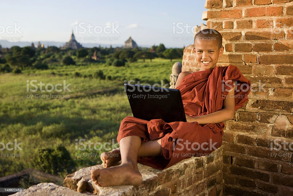 Young Buddhist monk using computer stock photo