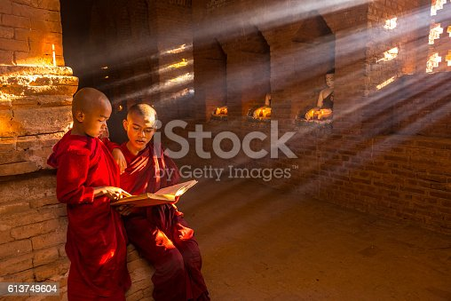 Two young buddhist monks praying inside the temple in Bagan, Myanmar
