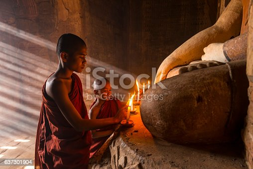 Two young buddhist monks praying inside the temple in Bagan,