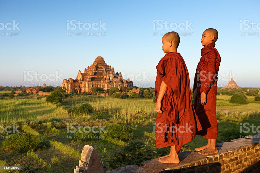Young Buddhist monks looking at the sunset, Bagan, Myanmar