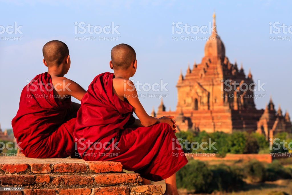 Young Buddhist monks resting on the temple, Myanmar stock photo