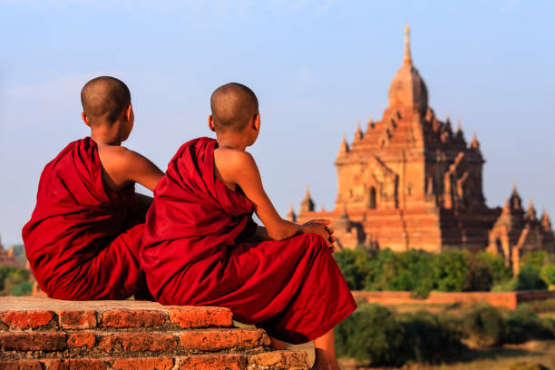 Young Buddhist monks resting on the temple, Myanmar Young Buddhist monks sitting on the temple and looking at the view of ancient Bagan, Myanmar (Burma) myanmar stock pictures, royalty-free photos & images