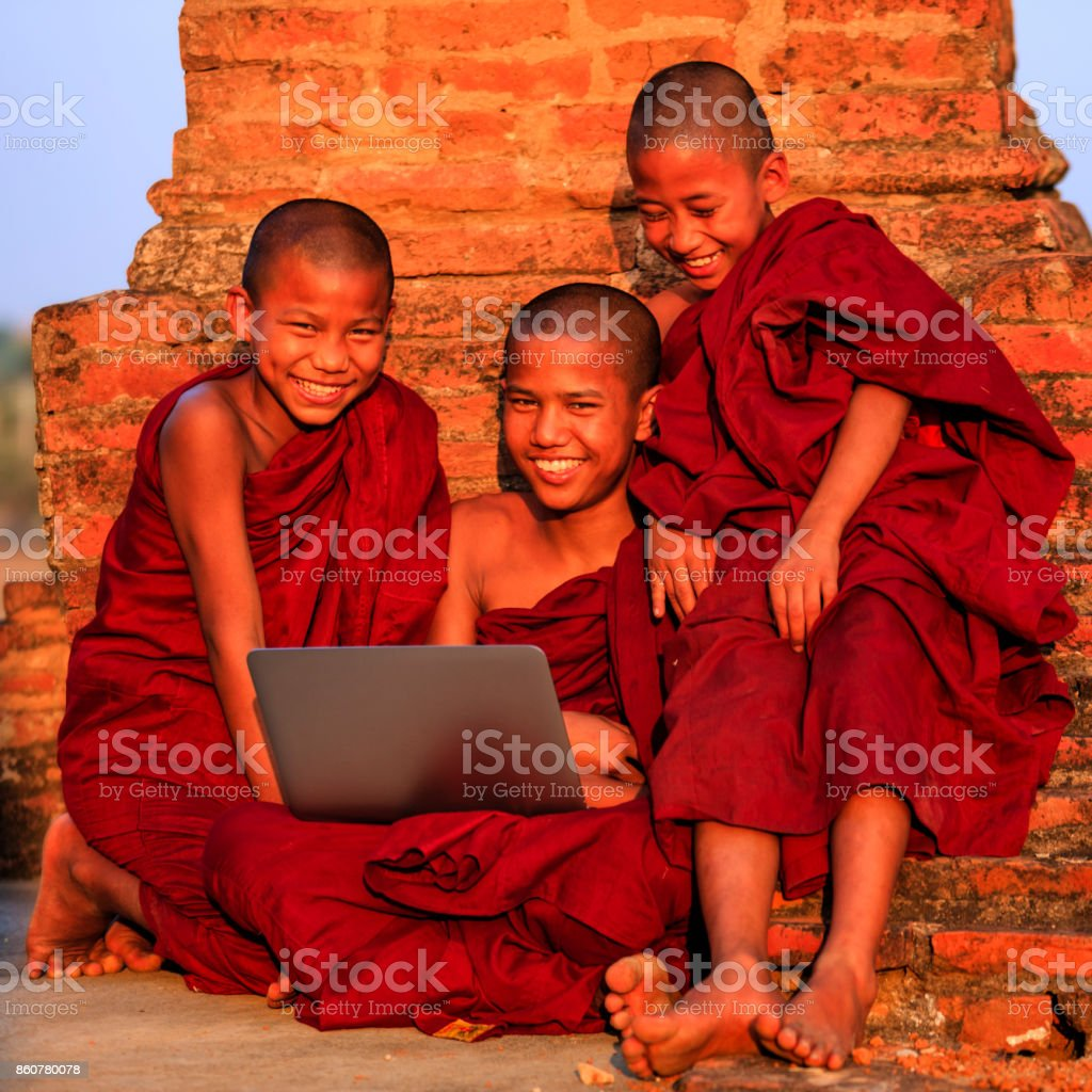 Young Buddhist monks using laptop stock photo