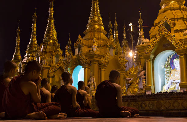 Young Buddhists praying in Shwedagon Pagoda, Myanmar stock photo