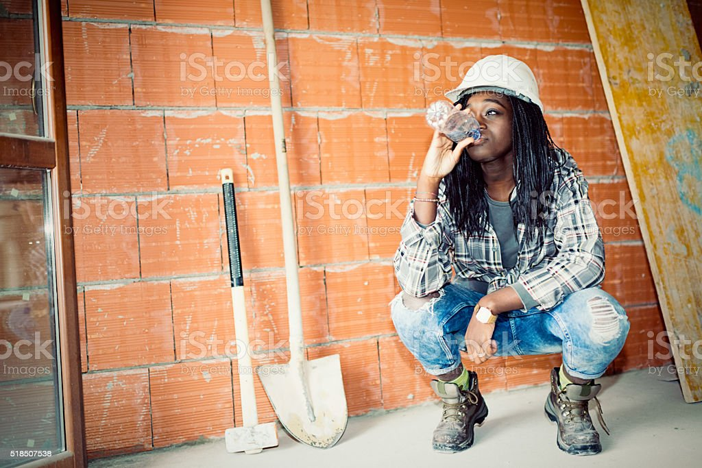 Young builder African woman drinking water at work place stock photo