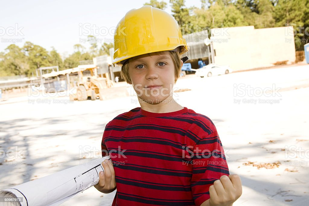 Young builder at job site with blueprints and hardhat royalty-free stock photo