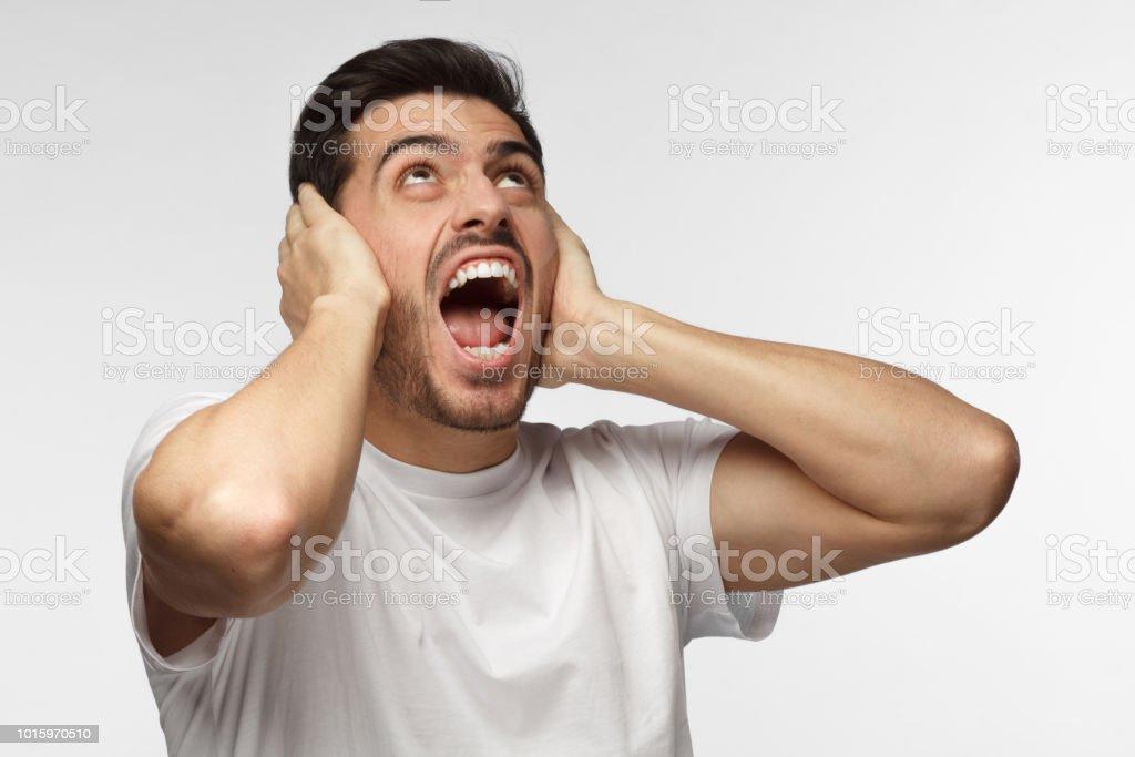 Jóvenes intimidan hombre grito a vecinos ruidosos, por ruido, cerrando los oídos con ambas manos, evitar lucha escucha - foto de stock