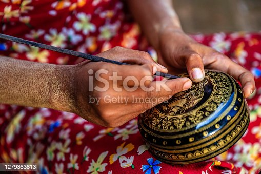 istock Young Burmese girl making a lacquerware in Bagan, Myanmar 1279363613