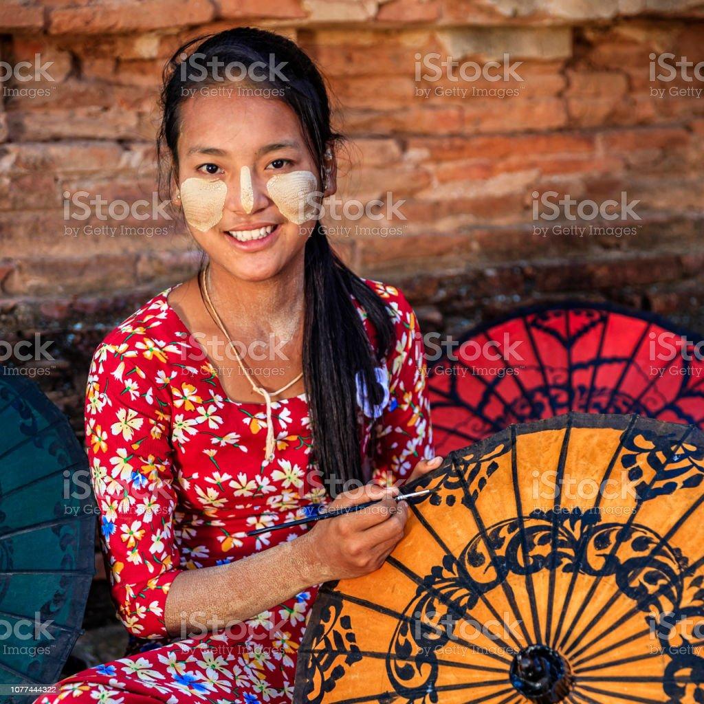 Young Burmese Girl Painting Colorful Umbrellas In Bagan
