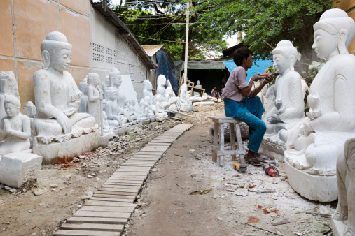 Young Burmese man carving a large marble Buddha statue