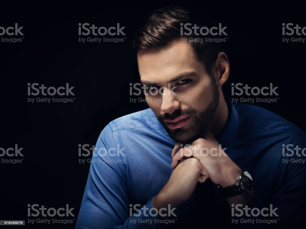 Young businesman portrait on black background stock photo