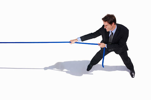 Young business adult pulling a rope on white stock photo