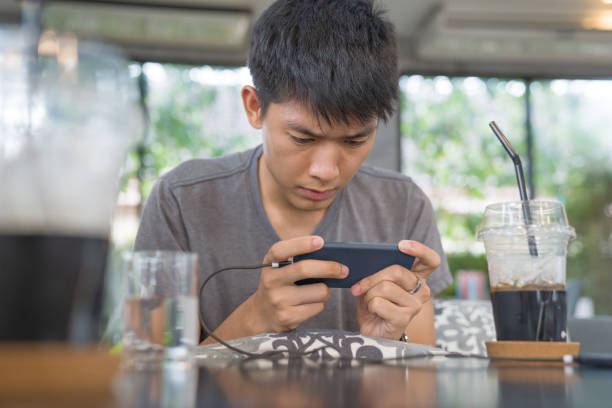 Young business Asian men using smart phone playing mobile game and relax with online shopping in his vocations stock photo