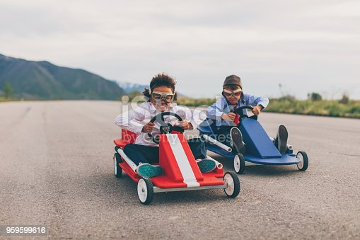 A young business girl races a boy dressed in business attire and race goggles in a push cart down a rural road in Utah. These business children love racing and competing and working hard for the success of their business. The young business boy struggles to beat the girl.