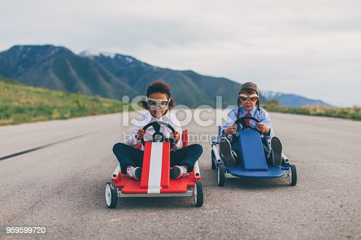 959599892 istock photo Young Business Boy and Girl Race Cars 959599720
