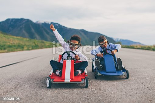 959599892 istock photo Young Business Boy and Girl Race Cars 959939108