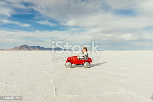 A young boy and businessman dressed in a business suit drives his vintage toy car on the salt flats located in Utah, USA. He is excited to race his business into profitability to the next travel destination.