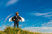 A young British boy dressed up in a business suits wears a jetpack while standing confidently on a grassy hill in England. The sky is the limit for this young businessman who dreams of accomplishing a profit with his entrepreneurship. Image taken in Gloucestershire, England.
